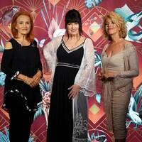 Trois femmes devant une tapisserie avec des motifs de feuillages et d'animaux.
