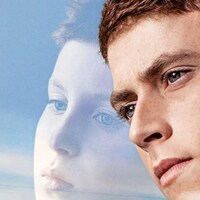 Un jeune homme, la tête appuyée contre une vitre dans la transparence de laquelle on voit son visage, enfant.