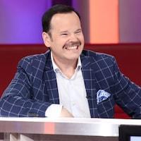 Un homme qui sourit. Il porte une chemise blanche et un veston bleu à carreaux.