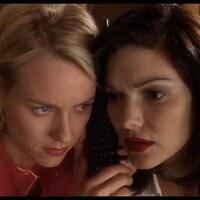 Une femme blonde et une femme brune écoutent ensemble dans le même combiné de téléphone.
