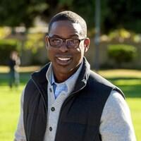 Un homme souriant est debout dans un parc.