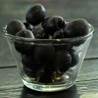 Un petit bol d'olives noires sur une table de bois.