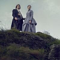 Claire Fraser et Jamie Fraser en haut d'une montagne, qui regardent au loin.