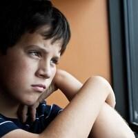Un garçon regarde par la fenêtre avec un air penseur.