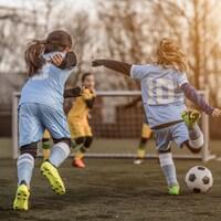 Deux jeunes filles s'apprêtent à marquer un but au soccer.