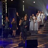 Il chante sur scène et une chorale chante derrière lui.