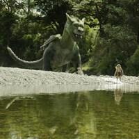 Un immense dragon vert joue avec un petit garçon sur une plage, devant un lac, dans une forêt.