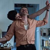 Dans un salon, deux hommes souriants dansent ensemble, l'un embrasse l'autre dans le cou.