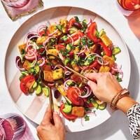 Une assiette de salade aux tomates, tofu, olives, concombres, oignons, et herbes, sur une table où on voit les mains d'une femme qui fait le service avec des ustensiles.