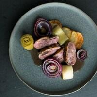 Une assiette de poitrine de canard aux poireaux et aux oignons rôtis avec sauce au vin rouge.