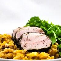 Le risotto est servi avec des tranches de porc et une salade de roquette.