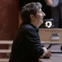 Robert Lepage est appuyé sur le bord de la scène.