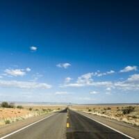Une route, des champs et le ciel bleu