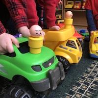 Trois enfants non identifiés d'âge préscolaire jouent ensemble avec des camions-jouets dans un service de garde.