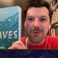 Il est en vidéoconférence devant une bibliothèque, il tient le livre « In Waves », d'AJ Dungo.