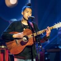 Un homme qui chante en jouant de guitare.