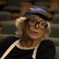 Elle est assise dans les sièges d'un théâtre et porte une casquette.