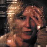 Une femme, la tête dans les mains, dans le reflet d'une fenêtre