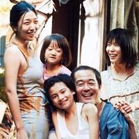 Une famille souriante, à l'extérieur.