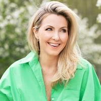 Une femme aux cheveux blonds qui sourit. Elle porte une chemise verte.