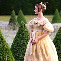 Une femme en robe de bal jaune, dans un jardin taillé.