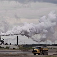 Un camion  travaille près de l'installation d'extraction des sables bitumineux de Syncrude près de la ville de Fort McMurray, en Alberta, le 1er juin 2014.