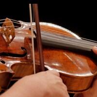 Des mains jouant sur son violon.