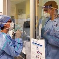 Deux personnels de soin se parlent derrière une vitre.