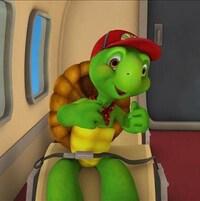 Benjamin est heureux, assis à un siège dans l'avion. Il est proche du hublot. Il porte une casquette rouge et un bandana à pois autour du cou.