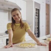 Alice est dans la cuisine et prépare une pizza.
