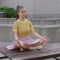 Alice est assise sur une table à pique-nique en position de méditation.