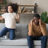 Père afro-américain ayant des problèmes avec une fille préscolaire coquine et bruyante. Elle saute sur un canapé et exige de l'attention. Le père fatigué se touche les temples.