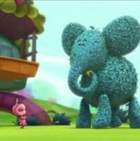 Au pied de la maison et d'un immense éléphant, Lily se tient debout, les yeux fermés, les bras croisés.
