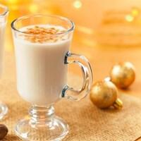 Deux tasses de lait de poule sont sur une table décorée pour Noël avec des noisettes, deux boules dorées et un napperon doré.