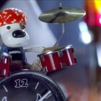 Une figurine de Bookaboo qui joue de la batterie sur un réveil matin