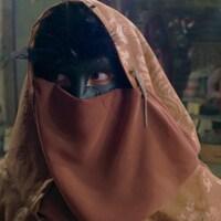 Gros plan sur étrange personnage enveloppé dans un cape et porte un masque noir sur les yeux.