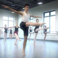 Dimitri danse le ballet dans un studio avec d'autres danseurs
