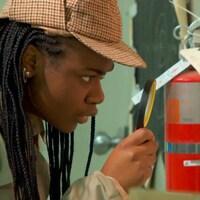 Malika inspecte un tableau à l'aide d'une loupe pour trouver un indice.