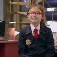 Elle sourit, elle est assise dans un bureau au quartier général