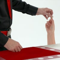 Gros plan sur la main de Daniel Coutu qui tient une pièce de monnaie.