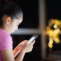 Une fillette regarde un téléphone cellulaire avec une attention soutenue.