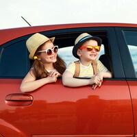 Ils sortent leur tête de la fenêtre, portent des lunettes de soleil et sourient.