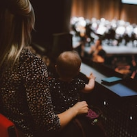 Une femme assiste à un concert de musique classique en compagnie d'un bébé assis sur ses genoux.