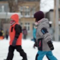 Des enfants dans une cour d'école l'hiver