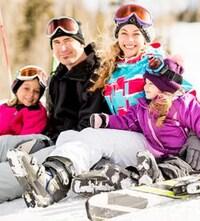 Une famille de quatre personnes en vêtements de ski.