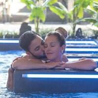 Un couple hétérosexuel s'embrassant dans une piscine.