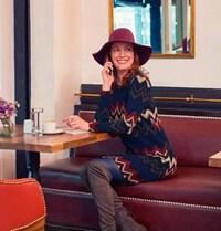 Une jeune femme souriante assise dans un café, habillée avec de beaux vêtements d'automne.