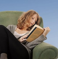 Une femme lisant un livre sur un sofa.