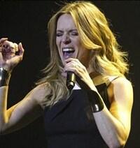 L'imitatrice et chanteuse Véronic DiCaire tenant un micro est en performance, la bouche ouverte.