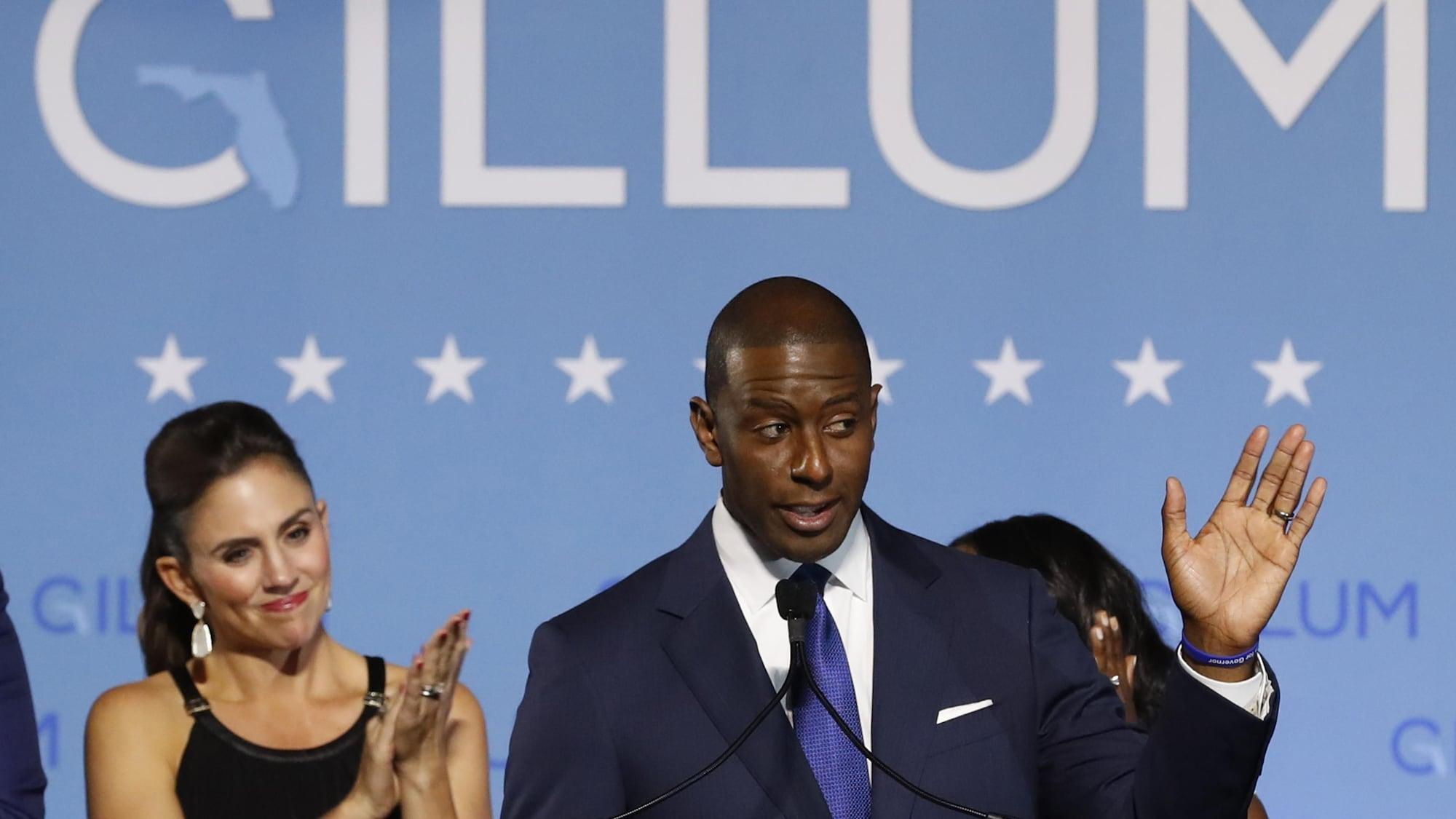 L'homme noir en costume bleu salue la foule de la main gauche. Derrière lui, une femme affiche un sourire contrit.